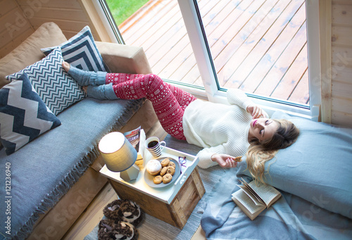 Obraz Young beautiful blonde woman with book lying down home by the livingroom window. Lazy cold day off concept - fototapety do salonu