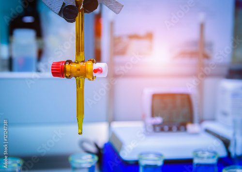 Fotografie, Tablou  Burette filled with yellow liquid in laboratory.