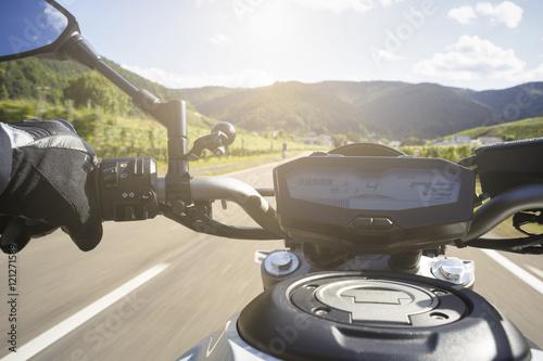 Plakat Motocyklista jeździ na drodze w lecie