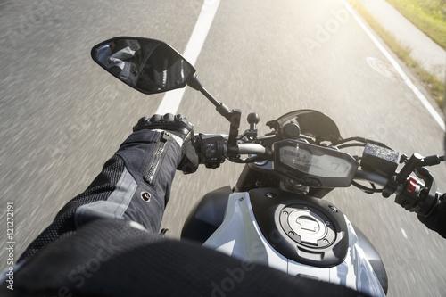 Foto  Motorradfahrer fährt auf Straße im Sommer