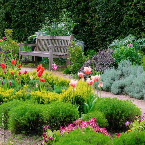 Plakat Ogród angielski ze ścieżką spacerową prowadzącą do pustej kompozycji kwadratowej ławki