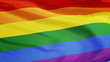 The gay pride rainbow flag waving against clean blue sky, close up, isolated with clipping path mask alpha channel transparency