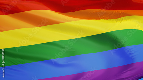 Foto  The gay pride rainbow flag waving against clean blue sky, close up, isolated wit