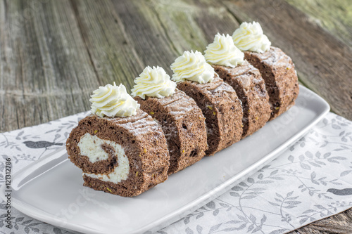 Fotografie, Obraz  Five pieces Chocolate roulade filled with whipped cream on white