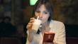 Young, pretty woman using smartphone and drinking coffee in cafe