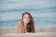 Cute girl with long hair and bow headband lying on the sand