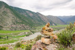 cairns or rock piles on the top of mountain overlooking loch in the highlands of Altai, Siberia