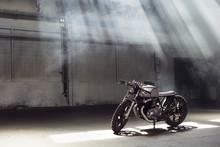 Motorcycle Standing In Dark Building In Rays Of Sunlight