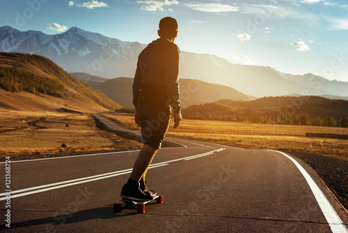 Man rides on longboard at sunset