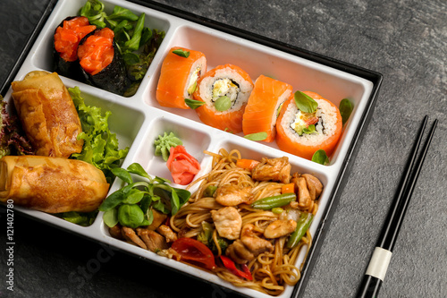 Traditional Japanese Bento lunch business. As part of the rice, sushi, vegetables, fish. Packaging is on a black background, next to chopsticks.