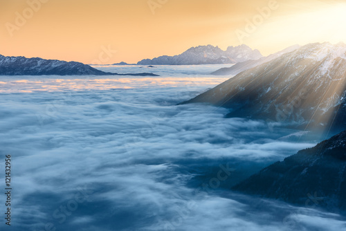 Fotografie, Tablou  Golden sunset over clouds and mountain peaks