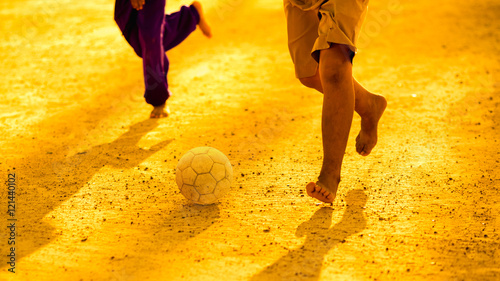 An action picture of the boys are playing soccer football in the sunshine day. Focus on the legs and ball.