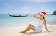 Christmas holidays on tropical sea shore. Young woman in santa claus hat sitting on the beach.