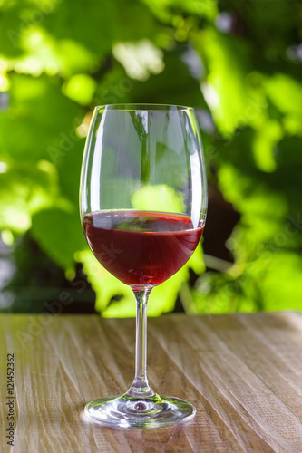 Stickers pour portes Pique-nique Glass of vintage red wine on a table, grapevine on background. Outdoor shot.