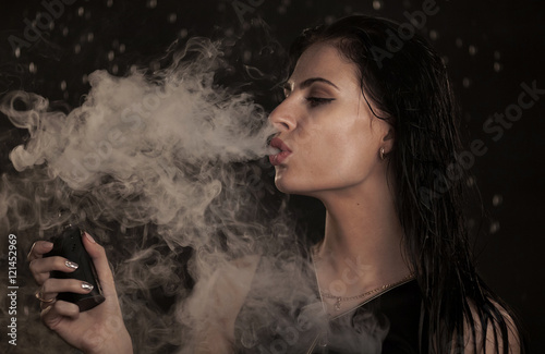 Young beautiful woman vaping e-cigarette. Water flowing on lwoman face.