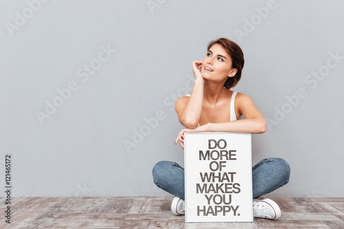 Pinturas sobre lienzo  Smiling woman sitting on the floor with motivational board