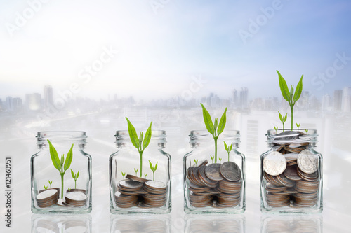 Fotografía  money coins and seed in clear bottle on cityscape photo blurred cityscape backgr
