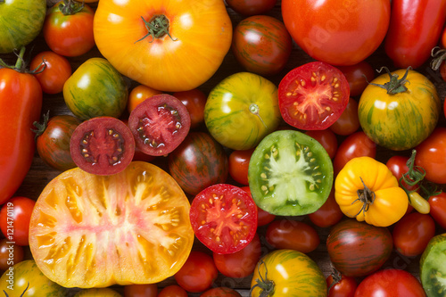 Fotografía  Close up of colorful tomatoes, some sliced, shot from above