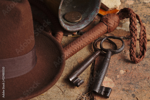 Fedora hat, bullwhip and relics on an antique tiled floor. Indiana theme