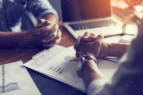 Fotografia  Hand, two men on a desk. Negotiating business.