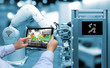 canvas print picture - Industry 4.0 concept .Man hand holding tablet with Augmented reality screen software and blue tone of automate wireless Robot arm in smart factory background