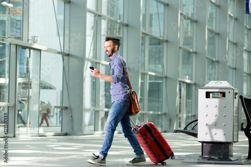 Fotografering  Man walking at airport with suitcase and mobile phone