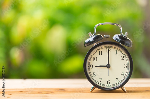 Fotografia  clock on wood table in the green garden time at 9 o'clock