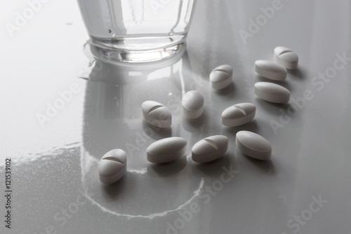 Painkillers and water glass on white surface.
