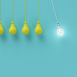 Leinwanddruck Bild - Hanging yellow light bulbs with glowing one different idea on light blue background , Minimal concept idea , flat lay , top