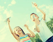 two happy kids playing with simple paper planes