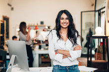Portrait Of Smiling Woman Standing In Modern Office