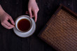 womans hands with cup of tea and rattan tray