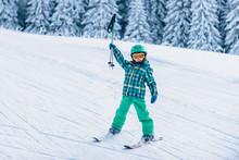 Little Skier Cheering, Holding Ski Poles Up