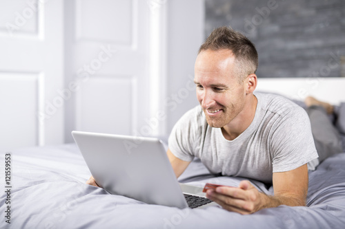 Photo  Serious casual young man using laptop in bed at home
