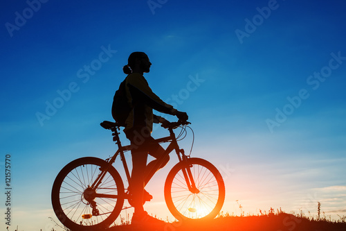 Aluminium Prints Cycling Silhouette of a bike on sky background