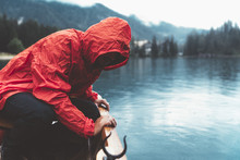 Man With Red Raincoat Is Watching The Water On A Wood Boat In Braies Lake