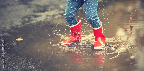 dziecko-w-gumowych-butach-skaczace-po-kaluzy