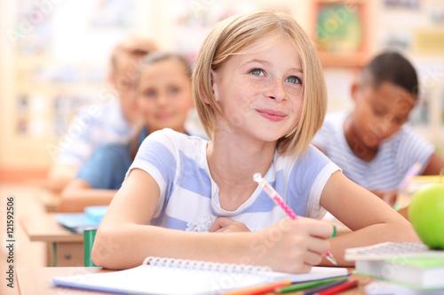 Fotografía  Cute schoolgirl in classroom on lesson