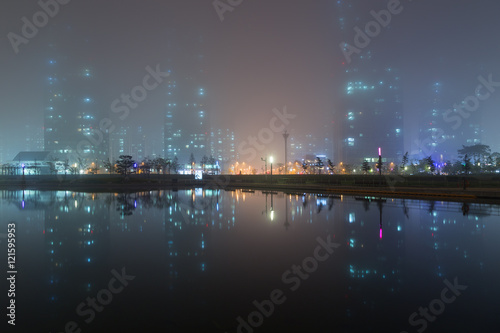 Foggy view of a park, skyscrapers and reflections on a lake in Incheon, South Korea in the evening.