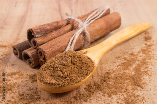 Fototapeta Powdery cinnamon and sticks on wooden table, seasoning for cooking obraz