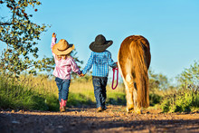 Little Cowgirl And Cowboy With...