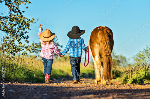Fotografie, Obraz Little cowgirl and cowboy with pony