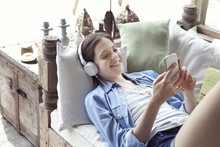 Young Woman Relaxing With Smartphone And Headphones