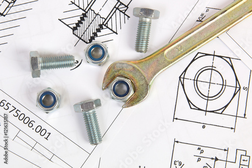 Fotografía  Wrench, bolts and nuts on background of engineering drawings
