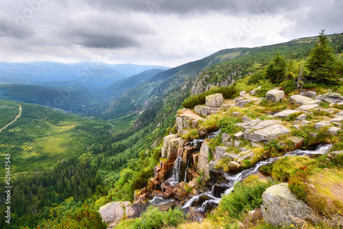 Fototapeta Beautiful waterfall above a deep green valley with mountains obraz