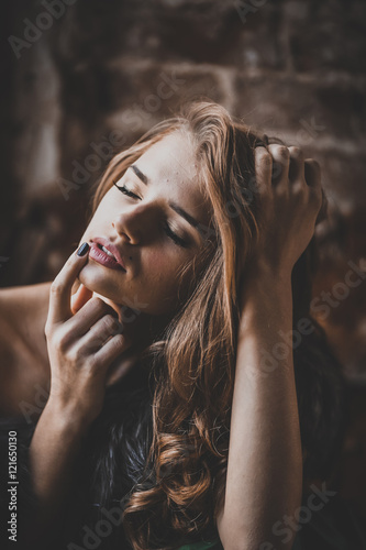 Poster Gypsy Close-up portrait of an attractive young woman by a dark grunge background. Beauty, fashion. Cosmetics, dark make-up. Long hair.