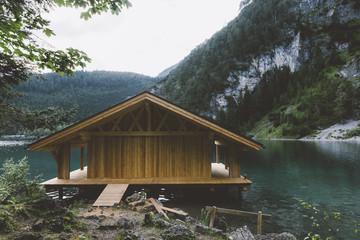 Fototapeta samoprzylepna Wood house on lake with mountains and trees