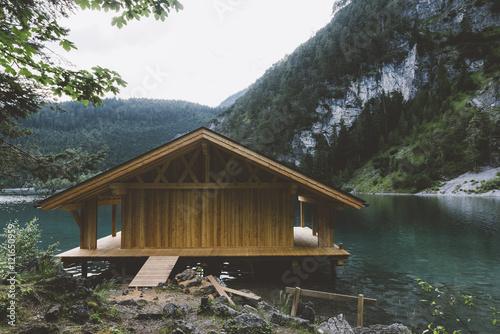 Drewniany dom na jeziorze z górami i drzewami