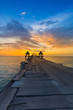 Wooden walk way leading to ocean with beautiful sunset sky background