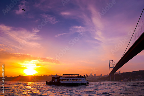 Bosphorus Bridge and excursion boat at sunset, Istanbul, Turkey. Poster